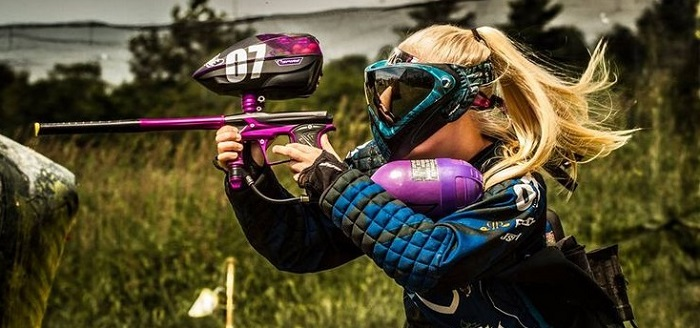 a blonde young woman playing paintball outdoors on a special field