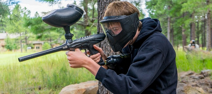 a young man holding a black paintball gun on a paintball field