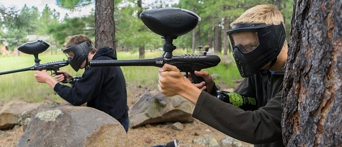 two young man playing paintball outdoors