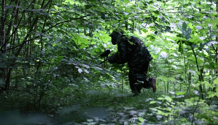 paintball player in a dense forest