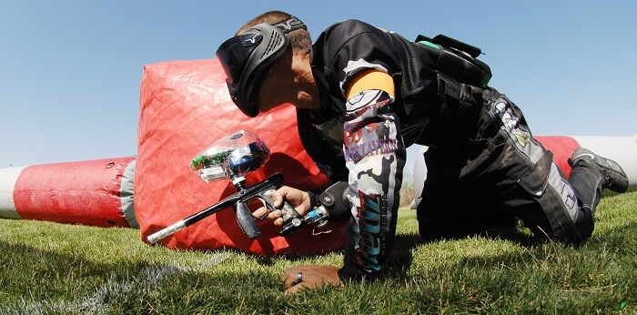 paintball player with paintball equipment snooping behind obstacle