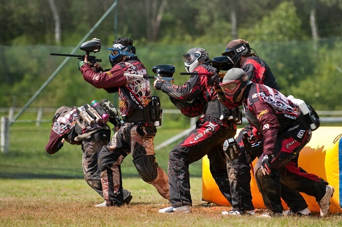 paintball team on paintball field with players equipped in paintball equipment with guns