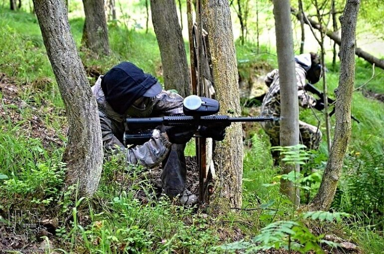 man in the woods playing paintball with a Woodsball gun
