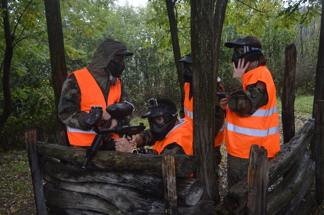 paintball team in the woods wearing protective gear and blaze orange vests