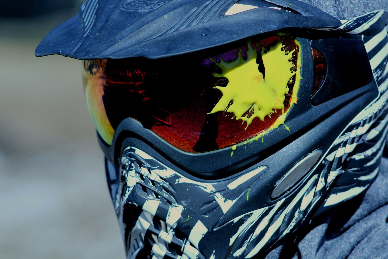Paintball mask on player with yellow paint on eye protection