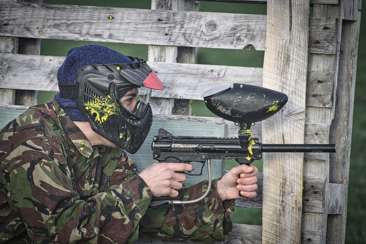 Paintball player hiding by a wooden fence with yellow paint on helmet