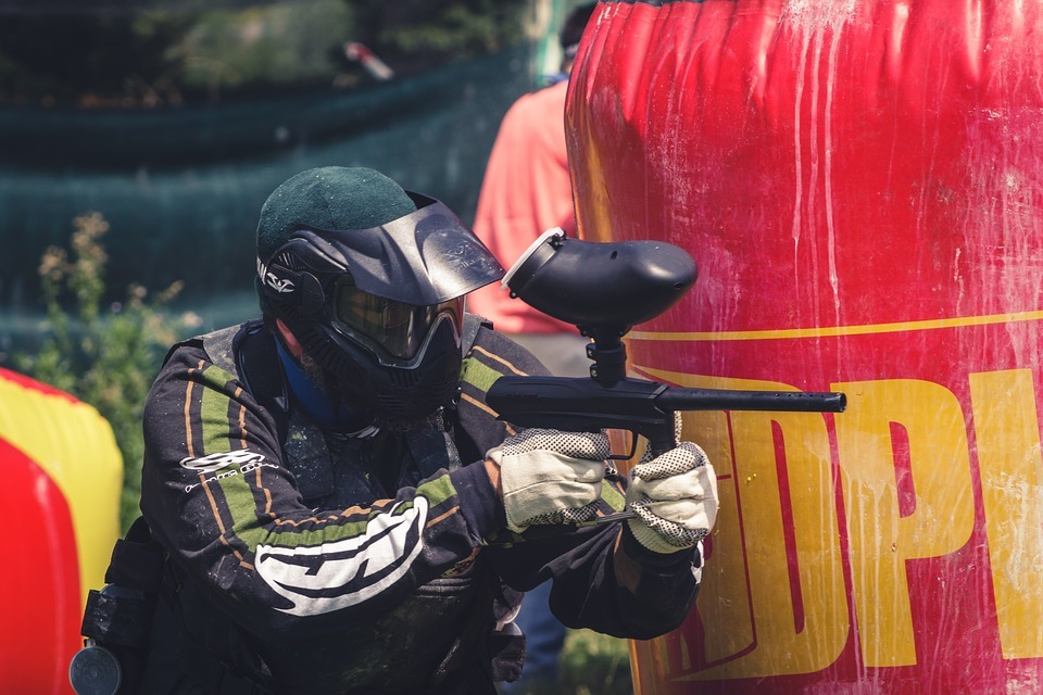 Man playing paintball wearing a paintball jersey