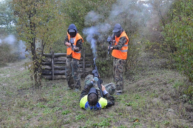 two paintball players pointing paintball gun towards an enemy lying on the ground