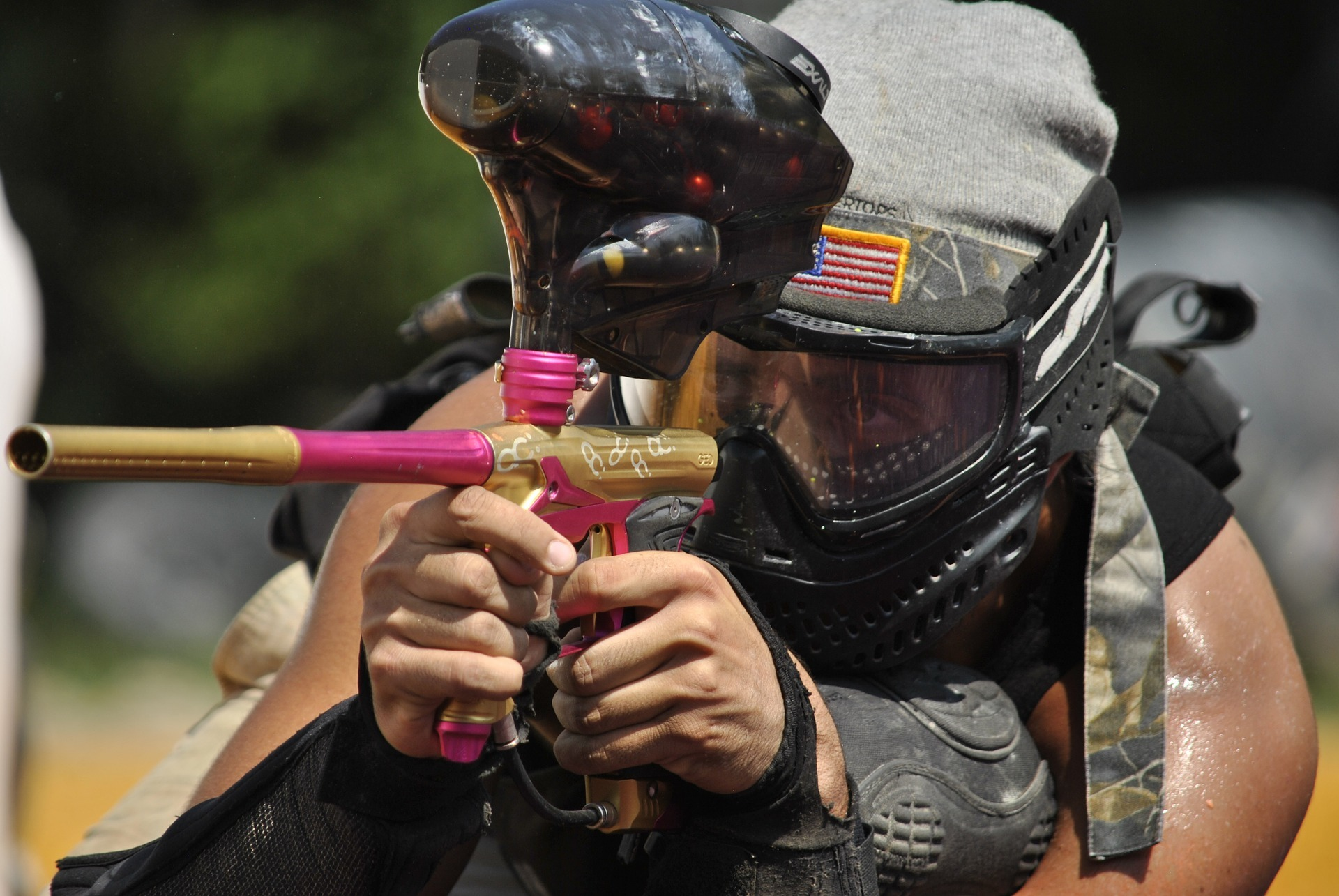 Man holding a paintball gun and wearing helmet is playing paintball