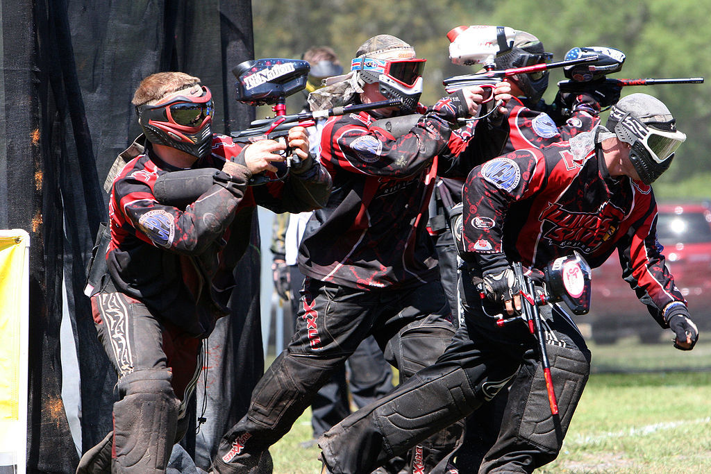 A group of guy playing paintball with paintball pistols.