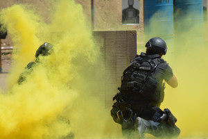 Yellow smoke clouds the area as guys with paintball pistols take aim at one another.